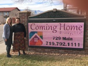 The Coming Home Realty co-owners, Carla Braddy and Jill Fredrickson, stand by the local Chamber of Commerce sign whose flashing marqee promotes their business at 729 Main Street, phone number 719.792.1111.